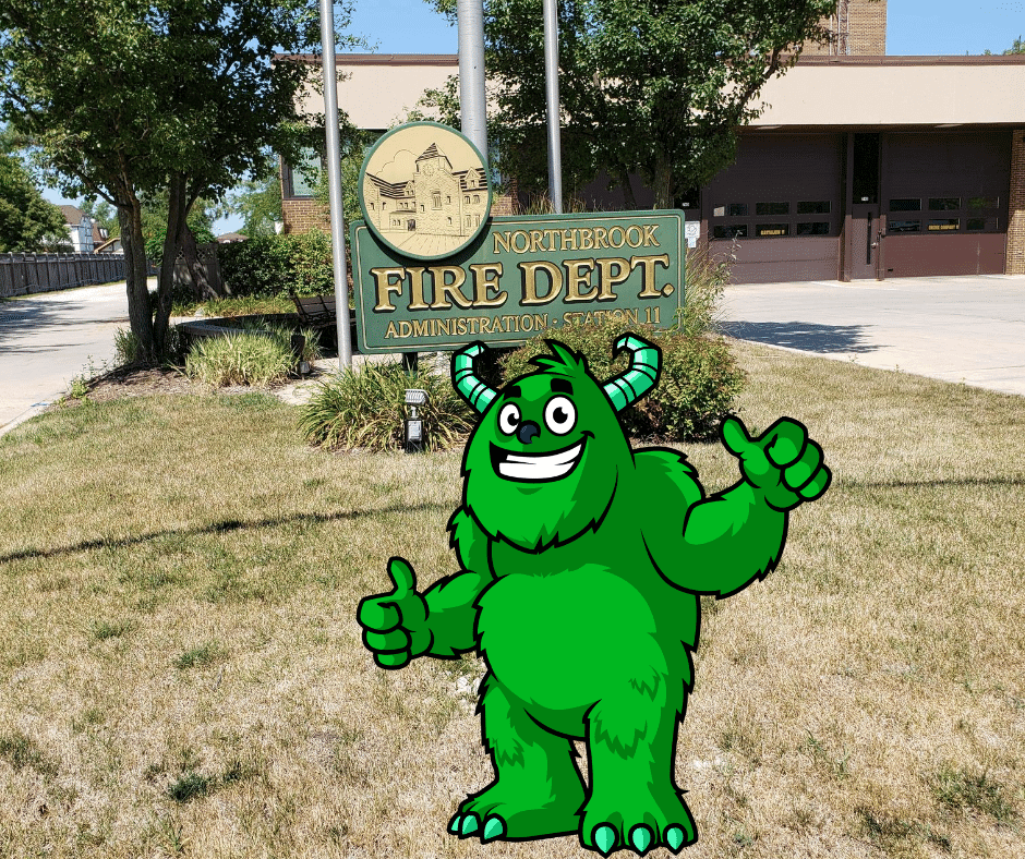 Mac the Dryer vent cleaning monster is standing in front of the Northbrook il fire department