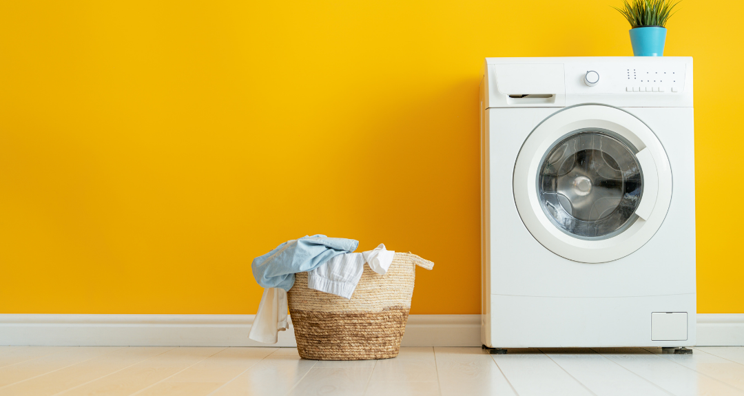 Dryer in front of a bright yellow wall with a laundry basket and clothes to the left
